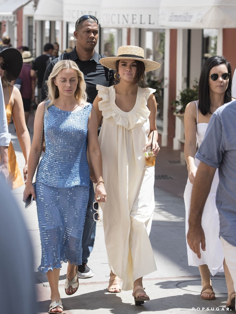 Selena Gomez packed the essentials for her Summer trip to Italy: maxi dresses, sandals, and a classic straw hat. A day after the actress celebrated her 27th birthday in Rome, she stepped out on the streets of Capri wearing yet another picture-perfect outfit for an afternoon out with friends. This time around, she opted for a beige dress with a ruffled neckline from Three Graces London. She tied the look together with gold hoop earrings, a Lack of Color brimmed boater hat, and Ancient Greek block heel sandals that we'd like to see in our own closets ASAP. Selena's vast shoe collection is understandably the object of much envy. It's true, she's partial to a towering sandal (peep the espadrilles she wore in Rome the day before) but you can also catch her in slides, sexy stilettos, or lace-up thigh-high boots. Whatever fits her fancy!  Keep reading to seem more photos of Selena's entire holiday outfit, and if you're ready to follow in her stylish footsteps, shop her exact pair of shoes below.