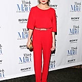Model Chrissy Teigen committed to the trend in a bright red jumpsuit with a figure-flattering cinched waist and slim-fit pant leg.