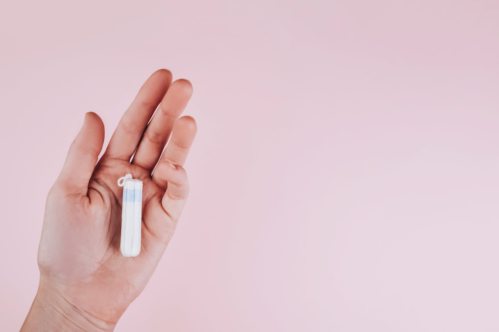 White tampon in a female hand on a pink background with place for text