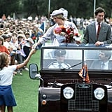 Princess Diana picked up a gift from a young fan as she rode in a Land Rover at the Hands Oval sportsground in Bunbury, Australia, in April 1983.