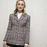 Wearing a tweed blazer with a white blouse and black shorts.