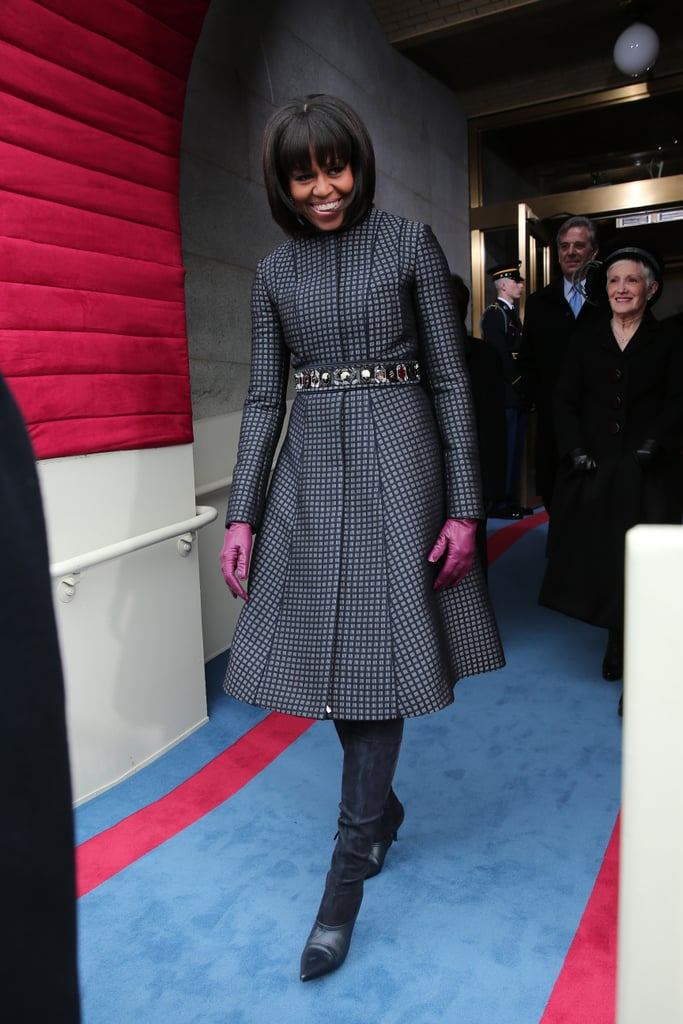 Michelle Obama is wintry perfection as she steps out at the Capitol. She kept the Thom Browne coat, belted it with a J.Crew embellished belt, added suede knee-high boots and berry-hued gloves, and made us fall in love with her all over again.
