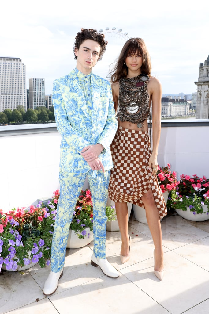 """Zendaya and Timothée Chalamet played a huge factor in getting us excited about the release of their new film Dune, which arrives in theatres on 22 Oct. Throughout the press tour for the film — which took the cast from Venice to London — not only did we get more glimpses of the actors' budding friendship, but we were also treated to some of the most exciting red carpet fashion we've seen in years.  The press tour kicked off at the Venice International Film Festival on 3 Sept. After doing a joint photocall with the film's cast, Zendaya and Timothée wowed fans — no really, how could anyone forget Zendaya's wet-look Balmain gown — when they walked the red carpet together for a screening of the film. Timothée looked equally striking in a shimmering black Haider Ackermann suit and Cartier jewels.  From Italy, the cast moved on to France for the film's Paris premiere, where the duo coordinated in cool-toned ensembles that gave us major disco vibes. Zendaya took our breath away yet again in a decadent aubergine coordinated set from Alaïa's winter/spring 2022 collection, while Timothée rocked a denim Tom Ford suit.  The next stop on the tour was London, where Zendaya and Timothée both opted for British designers for a photocall on Sunday, 17 Oct. """"When in London…wear @viviennewestwood,"""" Zendaya wrote of her look on Instagram, which was a top and skirt set from the Andreas Kronthaler for Vivienne Westwood spring 2020 collection. And we see why she chose this specific outfit: the chain-covered bodice and asymmetrical checkered skirt had a post-apocalyptic feel, perfectly in line with the film's theme. Timothée, on the other hand, chose a more whimsical ensemble for the occasion. His custom suit and shirt were inspired by a dress from the Stella McCartney summer 2021 collection that featured the same blue-and-yellow mushroom print.  Keep reading to see these looks from all angles, as well as the rest of Zendaya and Timothe Chalamet's best style moments from the Dune press tour."""
