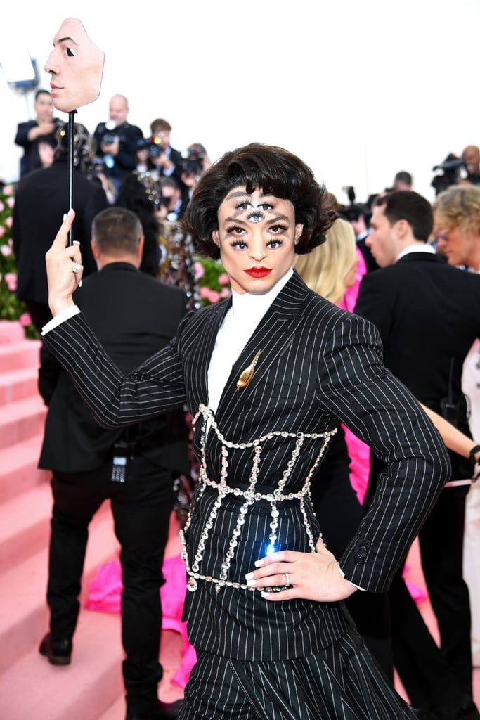 "I'll just come right out and say it: Ezra Miller was born for the Met Gala, so his debut on May 6 was extra special. The 26-year-old actor isn't shy about his love for over-the-top style (uh, remember when he walked a red carpet dressed as Hedwig?), and the ""Camp: Notes on Fashion"" event in NYC was right up his alley. Ezra teamed up with Burberry Creative Director Riccardo Tisci for his truly unique outfit. He held a mask to hide his face and wore a full cape, but underneath, he revealed a pinstripe suit with a dramatic train and jeweled corset. However, the real ""eye-catcher"" (pun very much intended) came from the five eyes painted on his face. A little spooky? Hmm, perhaps. A little genius? Absolutely. Keep reading to see more of Ezra's daring look. We hope to see his singular sense of style at many Met Galas in the future."