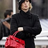 Zara keeps warm in the rain in Cheltenham in a chic hat and black coat. She accessorised with a red patent Mulberry bag.