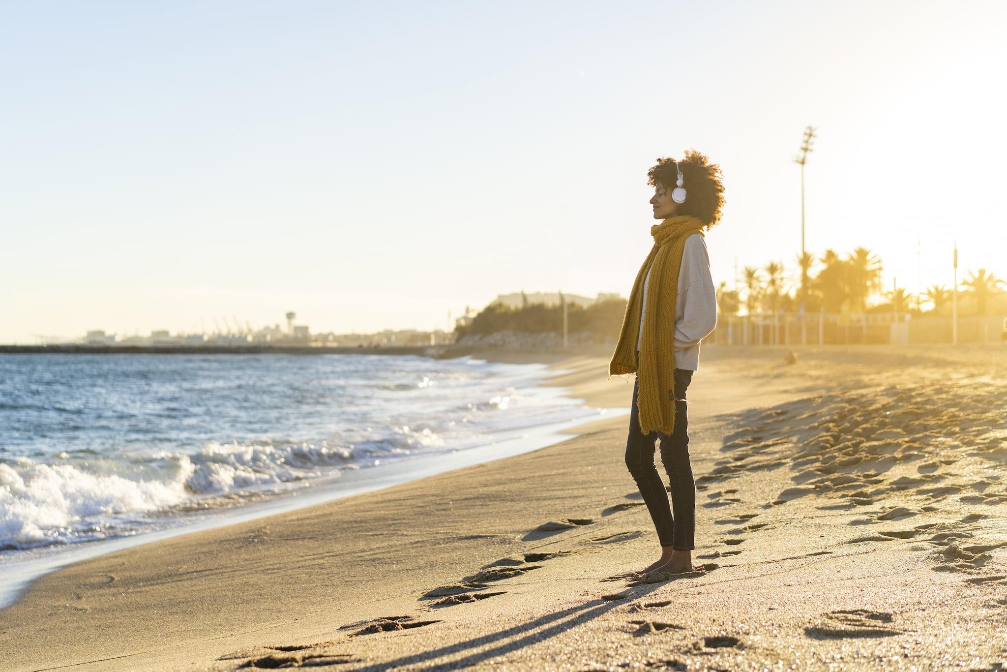 Woman at the beach, wearing headphones, listening music