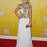 Carrie Underwood knows how to have a princess moment — and she's definitely had yet another one at the CMAs. This time, she chose a Reem Acra gown fresh from the designer's Spring 2013 show. The gold gown got its edge via the gold floral appliqué detailing on the front, which injected a gilded vibe to Carrie's entire look.