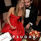 Jennifer Aniston cuddle up to fiancé Justin Theroux at Vanity Fair's Oscar afterparty.