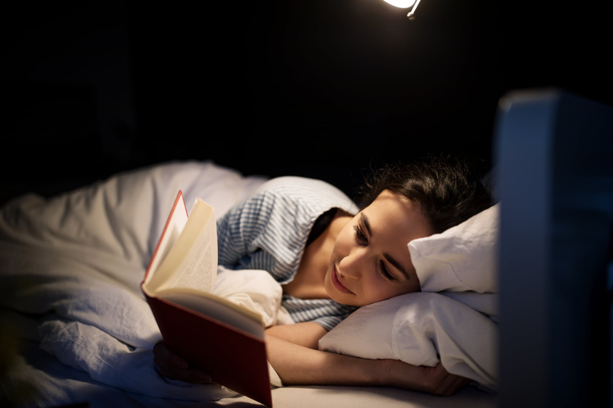 Young woman lying in her bed reading a book at night