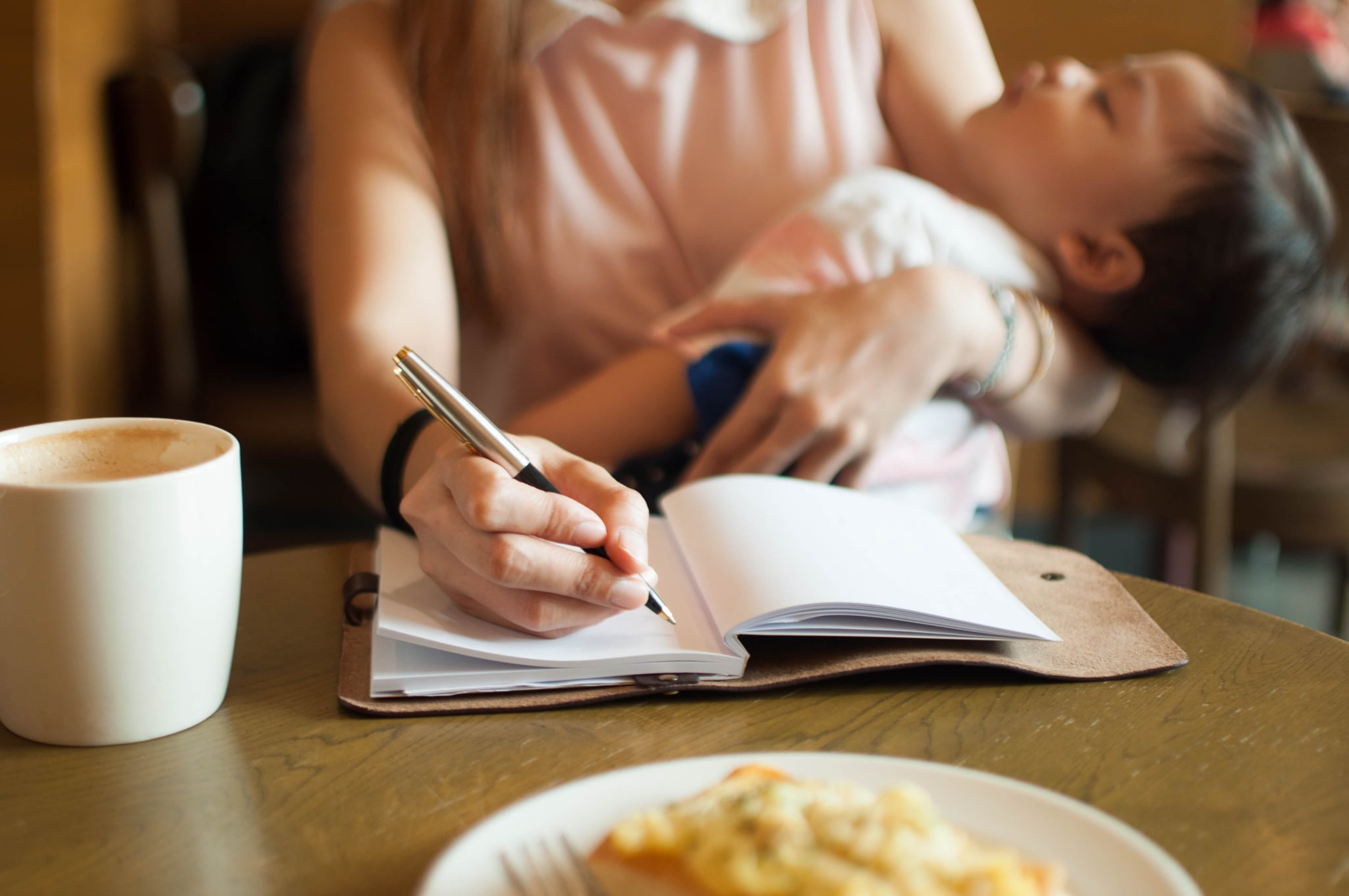 Working mom with her sleeping son on her arm while writing on a note pad