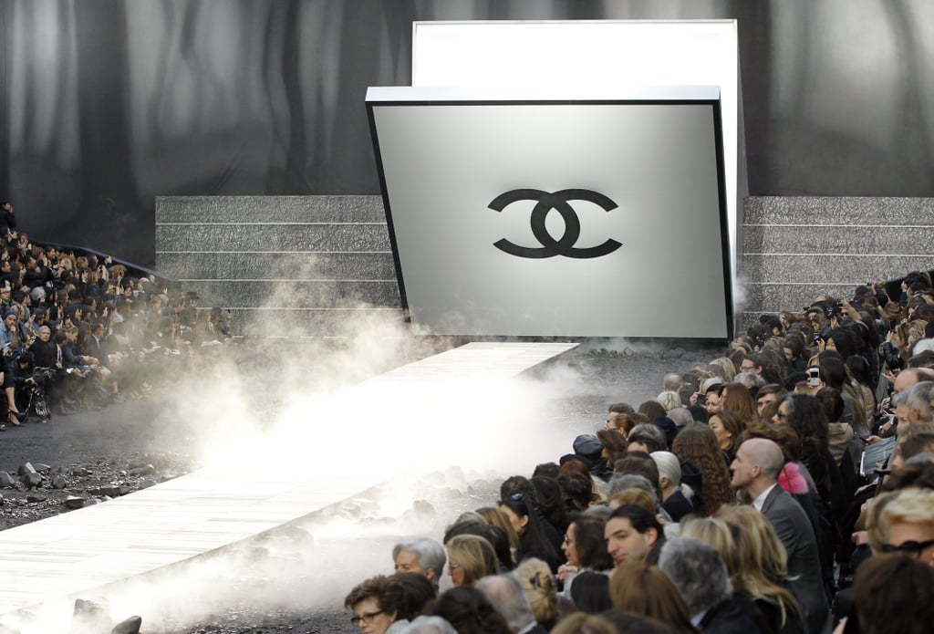 Karl Lagerfeld has gone crazy for jumpsuits for the latest Chanel collection in a variety of fits, all with statement pockets. A drawbridge opened at either end of the catwalk, which was surrounded by tons of charcoal and lumps of smoking black rock. There was an apocalyptic feel to the collection, which was mainly produced from a dark colour palette. Dresses were generally maxi length and produced from sensual fabrics like lace and tulle. There were long capes and boxy jackets, and even the most feminine pieces were given edge with applique and leather panels.   Trends: Jumpsuits, monochrome.  Colours: Black, grey, white, red. Key Looks: Quilted black jumpsuit.  Accessories: Midi heels, small clutch bags, lace gloves, chain and leather handbags.  Who Would Wear It: Women who want an elegant rock-chic wardrobe with a tailored edge.