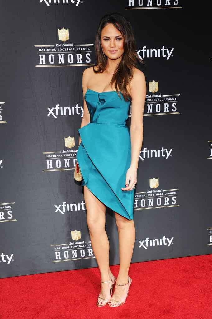 Chrissy Teigen worked a strapless teal minidress and sleek gold sandals at the NFL Honors event. But what did we love most about this seemingly minimalist-cool cocktail number? The asymmetrical-cut skirt, which showed off her enviable stems perfectly.