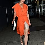 Katie Holmes stepped out in a bright orange chiffon shift dress, but didn't let the color overwhelm. Instead, she let a nude slip peek through, paired the look with a sleek nude T-strap sandal, and finished it off with a blue and white clutch.