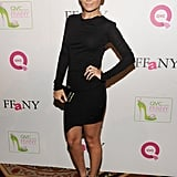 Nicole Richie in a black dress and leopard print heels.