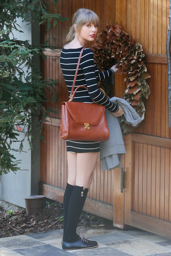 Taylor Swift arrived at a friend's house in LA yesterday. Taylor smiled as she left the house in a pair of black knee socks and a striped dress. Despite the happy look, Taylor has been dealing with some heartache. Taylor broke up with Harry Styles, her boyfriend of two months, while they were on holiday together in the Caribbean. The singer returned home after the split, while Harry stayed in the Virgin Islands for a few more days to party with celebrities like Richard Branson. Now Harry is back in England, having landed in his native country on Monday to continue working in the record studio with his band One Direction. Taylor is keeping busy as well by rehearsing for her upcoming tour and planning her performance for this year's Grammys, which will air on Feb. 11. She's also set to make an appearance at today's People's Choice Awards.