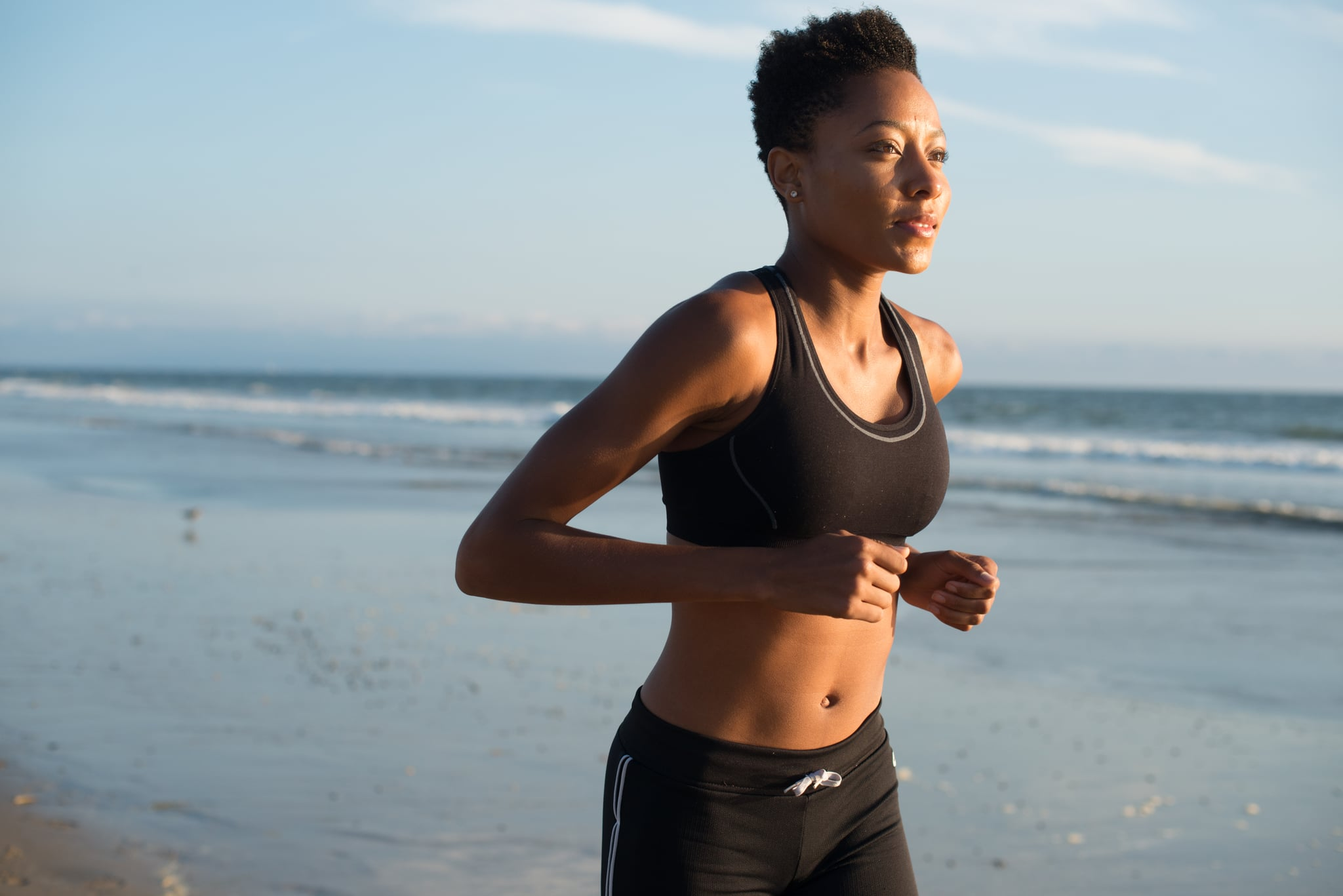 Black woman runs along the beach by the ocean