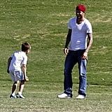 David Beckham and Cruz Beckham played on the sidelines of a soccer game.