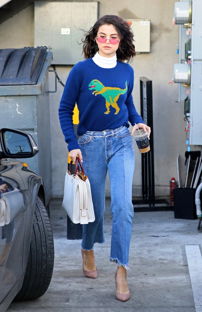 Kick-starting her partnership with Coach with a bang, the star showed off the brand's coveted dinosaur sweater with frayed denim and beige suede heels.