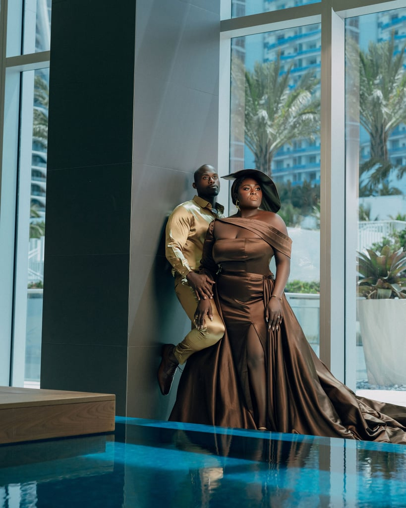 """Danielle Brooks needed the assistance of the industry's best and brightest to turn her engagement photo shoot with Dennis Gelin into an unforgettable production. Luckily, she had her trusty team's help, including the support of longtime stylist Kelly Augustine. You can thank Kelly for the unbelievable outfits Danielle showed off for the sexy shoot, from beaded bustiers to gorgeous red carpet-worthy gowns.  Kelly told POPSUGAR she felt """"humbled"""" when Danielle asked her to be a part of the styling for her engagement photos. """"It's one thing to style for press and editorial, but to style for a wedding is so intimate and personal. You have to really trust someone."""" Danielle trusted Kelly's vision for the shoot wholeheartedly and had the stylist take the reigns. They coordinated with photographer Kareem Virgo on locations and the wedding color palette, but one factor mattered above all else: """"[Danielle] just wanted to look hot!"""" Mission accomplished.  The actress wore several spectacular looks for her and Dennis's engagement shoot, and Kelly can't choose a favorite. How could you, when the options include a jaw-dropping hand-beaded corset by Edwin Reyes with over 8,000 hand-beaded pearls, an elegant custom brown gown from Nneka of Brides by Nona, and custom """"something blue"""" suits from Ilbert Sanchez of Garçon Couture.  Kelly said she can see comparisons to On the Run Part II and Queen & Slim, but the photo shoot's true inspiration is partnership. """"I think, in general, the idea of marriage is really just you and your partner against the world,"""" she explained. """"So we tapped into that energy and applied it specifically to Danielle and Dennis' personalities."""" Like most brides, Danielle is keeping her wedding look under wraps until the big day, but Kelly will definitely be with her. """"The only thing I can say is to expect her to look FABULOUS!"""" We wouldn't expect anything less.       Related:                                                                                       """