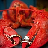 Tip: If your reception has a unique touch, like lobster dinner, incorporate it into a ring shot. Photo by Kathy Blanchard Photography via Style Me Pretty