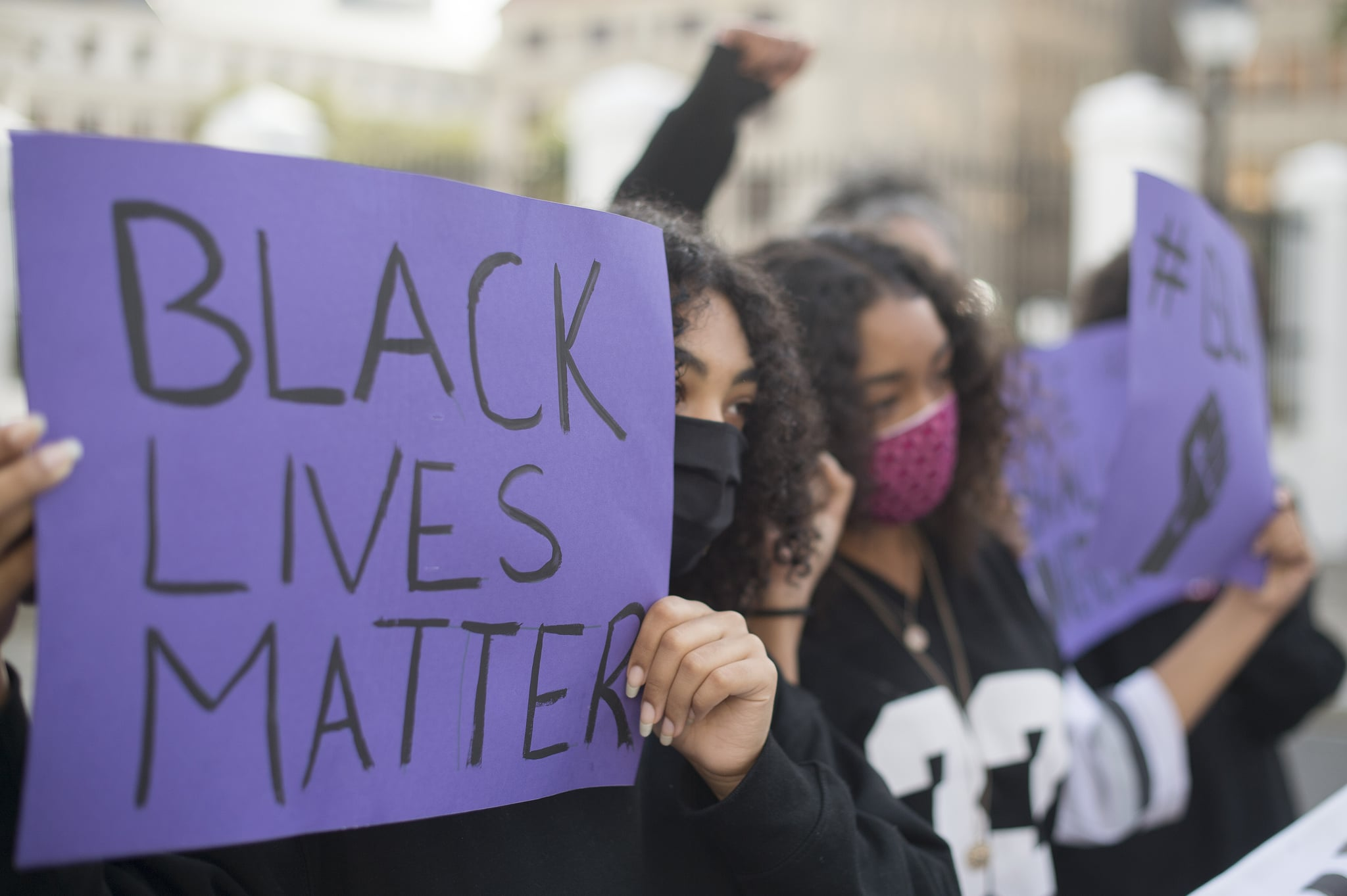 Protestors hold up placards during a protest against police violence, at the gates of the South African Parliament in Cape Town, on June 3, 2020. - This protest is in solidarity with the Black Lives Matter movement in the United States of America (USA), and around the world  following the death of George Floyd in police custody in Minneapolis. (Photo by RODGER BOSCH / AFP) (Photo by RODGER BOSCH/AFP via Getty Images)