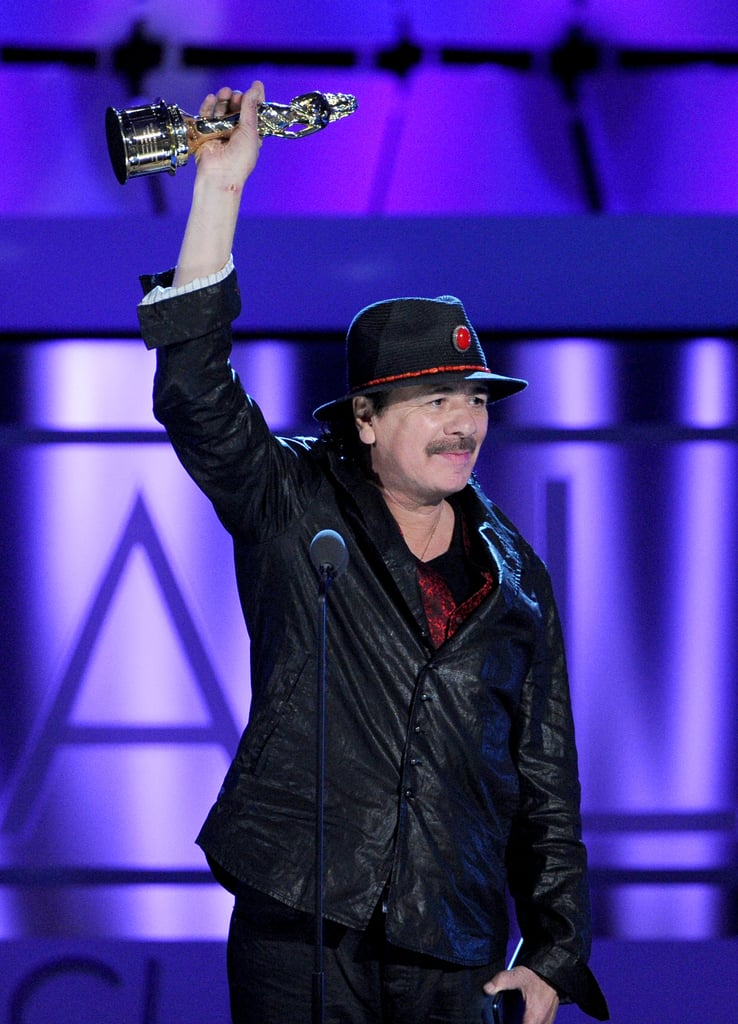Carlos Santana held up his award after he was recognized.