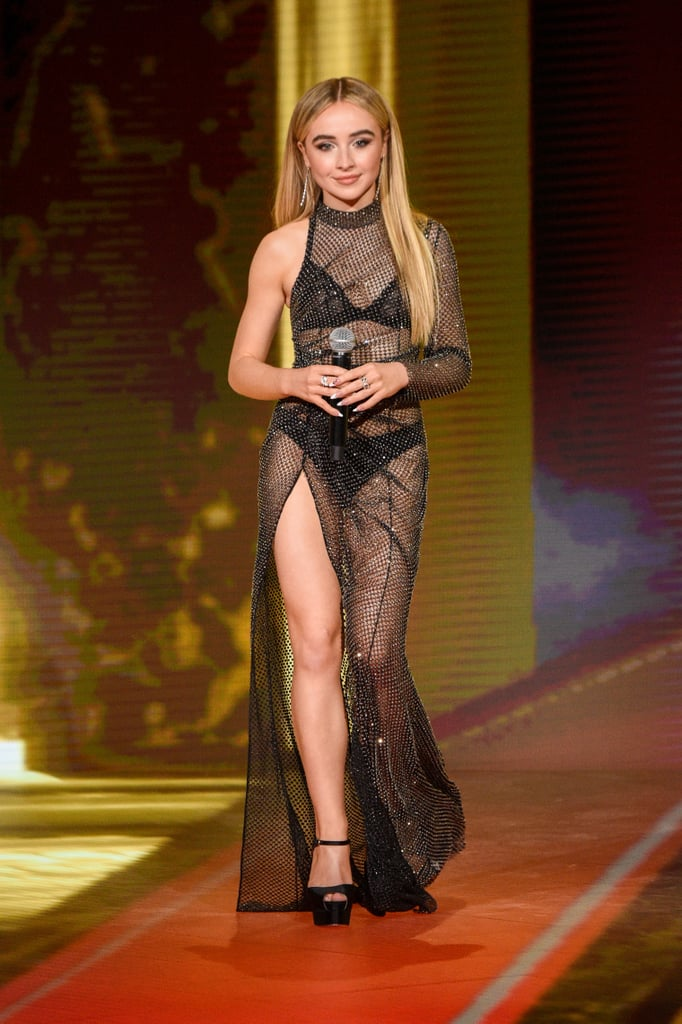 Sabrina Carpenter sure knows how to make a statement with her stunning bold looks! On Dec. 6, the 21-year-old singer and actress pulled up to present at the 2020 MTV Movie & TV Awards: Greatest of All Time wearing a showstopping Ralph & Russo asymmetrical gown. From head to toe, she had our attention. Sabrina rocked JustDesi Forevermark rings and earrings to match the shimmering sheer dress. And that dress? Well, from the turtleneck to asymmetrical sleeves and all the way down to the hip-length slit, we were obsessed. It's a good thing Sabrina was just presenting at the awards, because we're not sure she'd be able to do those epic Work It dance moves with such a look! It wasn't the typical award show on Sunday night, but it was a celebration to honor the best moments in film and TV from the '80s all the way through 2020. As for incredible red carpet award show outfits, we think Sabrina's Ralph & Russo dress just made it to the top of our list. Check out photos of the star at the 2020 MTV Awards ahead.      Related:                                                                                                           Lily Collins Steps Out of Character in a Sultry Black Latex Dress at the MTV Movie Awards