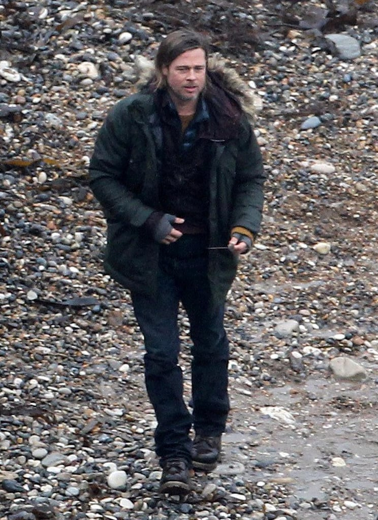 """Brad Pitt wore a big jacket this afternoon to work on World War Z near the beach on the south coast of England. He's been in the UK doing reshoots for the action film for the last few weeks. He and fiancée Angelina Jolie have gotten accustomed to being in England over the last few months, since she also shot Maleficent there. Their six kids are settled down there for the time being as well. It seems the location has allowed Brad and Angelina to catch up with some of their old British friends. Angelina hosted an event for Ewan McGregor, a Scot, in honor of what she's dubbed his """"honest"""" performance in The Impossible. She organized a special screening to celebrate Ewan's work last Sunday at London's Soho Hotel."""