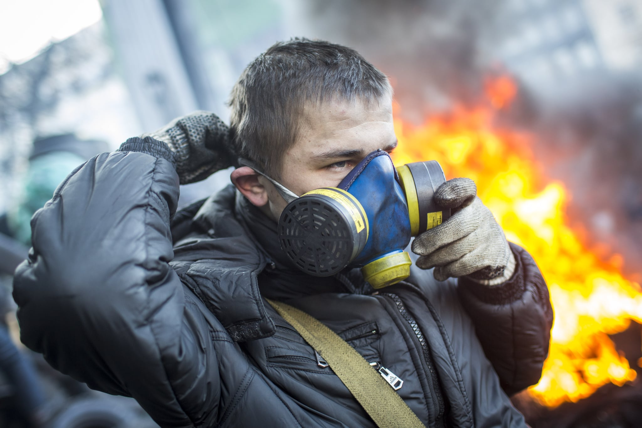 A protester put on his gas mask near the burning piles.