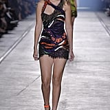 Gigi's form-fitting textured mini dress featured a strappy neckline, a frayed hem, and splashes of purple and orange. The design's shimmering details were played up by matching ankle-strap platform pumps.