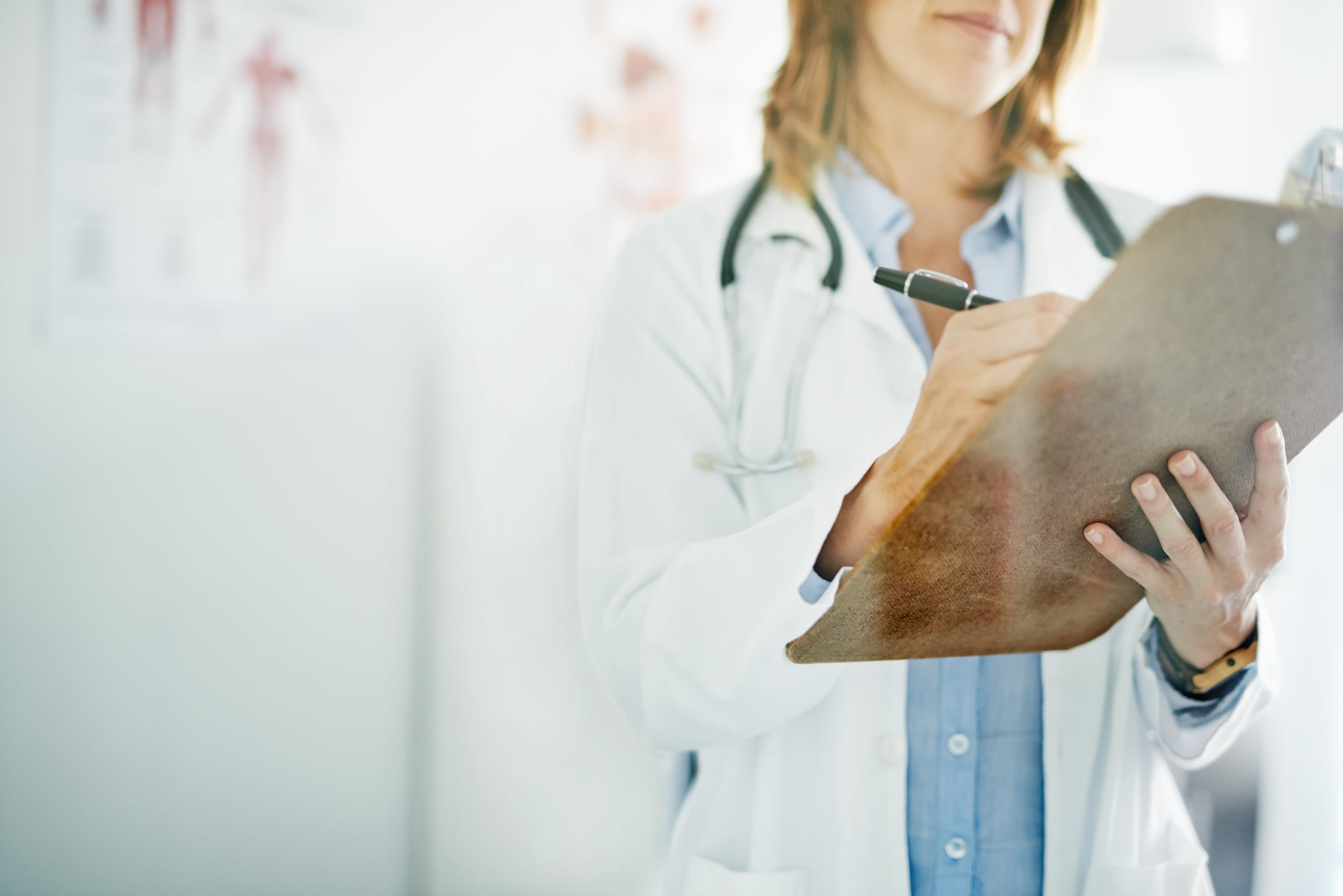 Cropped shot of a doctor writing on a clipboard in a consulting room