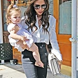 Victoria Beckham looked stylish as she carried Harper Beckham in NYC.