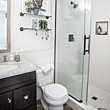 Incorporating lots of white and clear glass helped make the bathroom feel deceptively large and airy. If you have a small bathroom, take my designer's advice and opt for a clear glass door instead of a shower curtain or textured glass door. It instantly opened up more visual square footage, making our bathroom feel much less claustrophobic. The porcelain floor tiles look like reclaimed wood but can withstand tons of humidity and water — laying them in a herringbone pattern adds instant elegance.