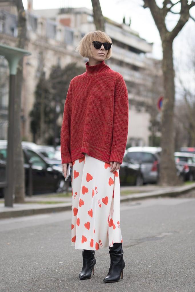 ارتدي كنزة حمراء فضفاضة مع تنورة مطبّعة