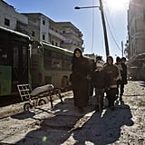 Syrians walk through Aleppo during the evacuation operation of rebels and their families on Dec. 15.