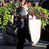 Zoe Buckman was all smiles toting baby Cleo into JFK's international terminal.