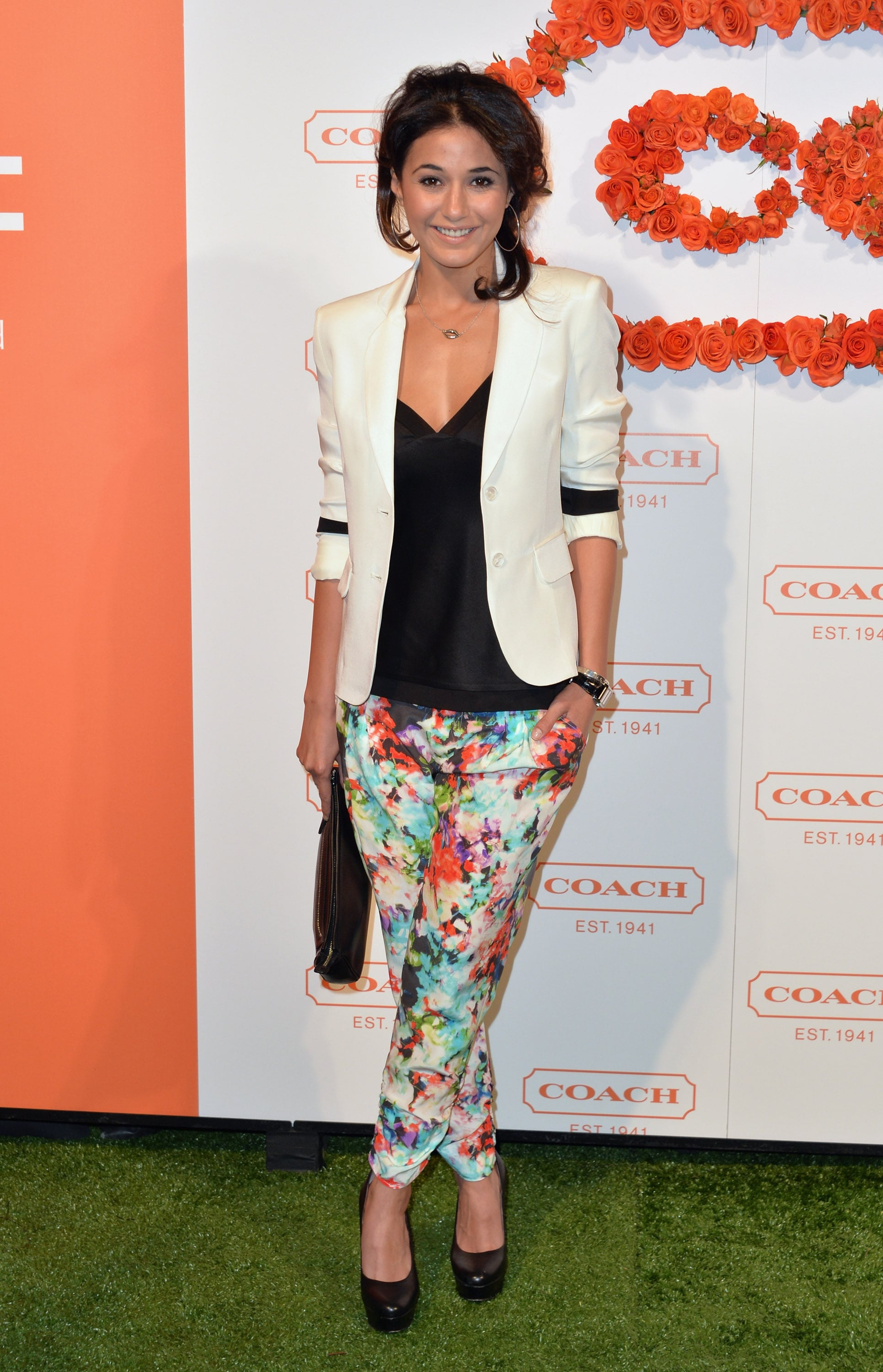 Emmanuelle Chriqui paired floral trousers with a tailored white blazer and black accessories at the Coach event.