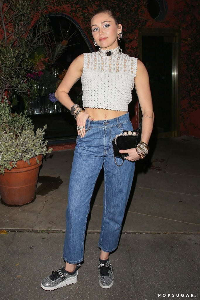Miley Cyrus's steps were sparkling on Jan. 25, when she showed up to the Miu Miu Women's Tales showing in Los Angeles to celebrate the film Shako Mako. The 26-year-old musician kept things casual on the red carpet and opted for a crochet crop top with straight-leg jeans — a style choice any modern-day hippie would love. Her shoes, however, were in a league of their own.  While it's easy to zero in on Miley's breezy top, please tear your attention away for just a second to focus on the real star of the show: her sparkling sneakers. These kicks from Miu Miu's Fall 2018 collection are like the high-fashion upgrade of your favorite shoes from elementary school. Miley is practically an expert in wild sneakers, thanks to her own Converse collections, so her choice for the event totally checks out.  Miley flaunted her glittery pair on Instagram while snacking over popcorn and pasta, like the true queen she is. She pulled the whole look together with a hair bow and a black velvet purse with pearl embellishments. How chic! Ahead, see even more glimpses of Miley's look and shop similar sparkling sneakers for yourself.      Related:                                                                                                           Miley Cyrus's Plunging Black Dress Shows Off All Her Sexy Tattoos