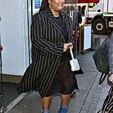 Lizzo makes even the simplest outfit look chic in these adorable denim boots and an oversize pinstripe coat. The only way to accessorize? With a glimmery silver purse, of course.