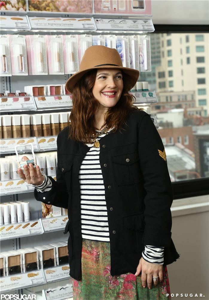 Drew Barrymore posed with her cosmetics collection in NYC Tuesday.