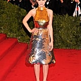 At the 2012 Met Gala, Carey sparkled in a silver-and gold paillette halter and satin pumps, both by Prada. She completed her red carpet style with minimal jewels and a polished updo.