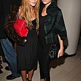 Twinning combo: For Balenciaga's 2006 Paris launch, the girls styled two different but equally chic cropped coats with their black-on-black looks.   Mary-Kate layered a cropped fur topper over her simple black dress while toting an oversize red clutch.  Ashley went preppy in tuxedo-stripe pants and a ruffled tartan coat.