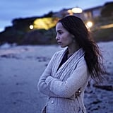 Zoë Kravitz as Bonnie Carlson in a knit cardigan and beaded drop earrings.