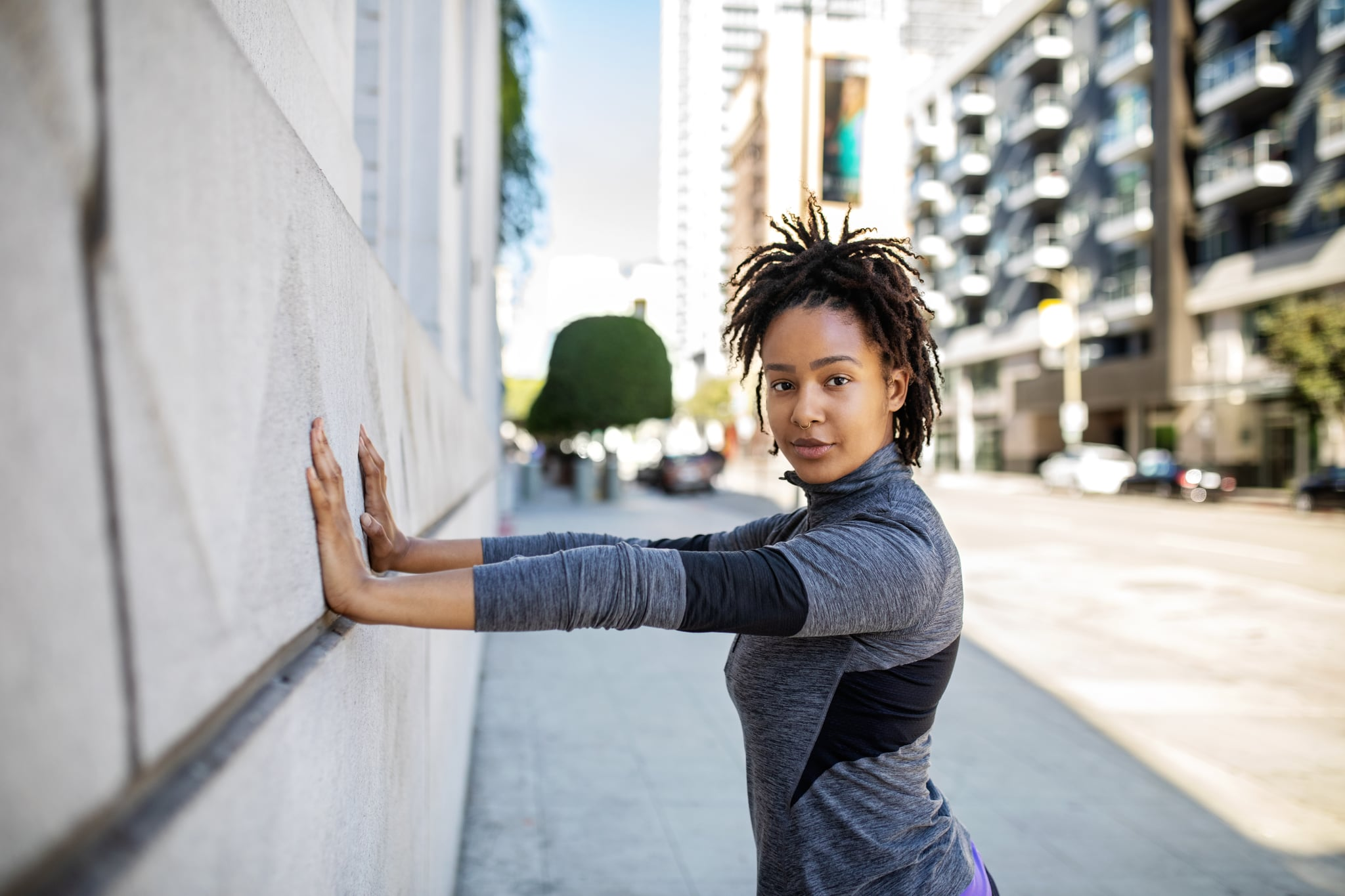 Portrait of a fit young african woman doing stretching workout against a wall. Fitness female exercising in morning outdoors.