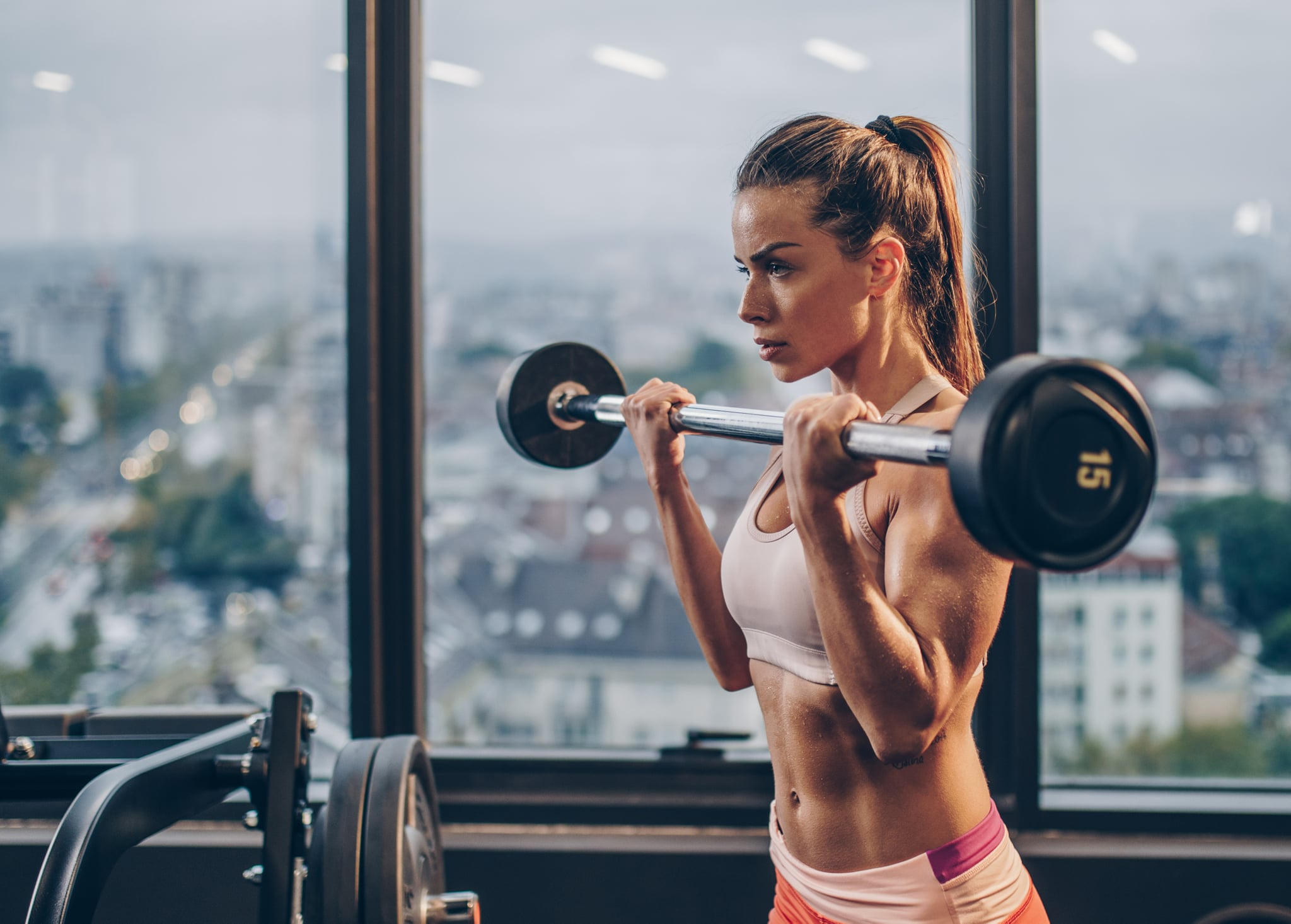 Young muscular build woman exercising with barbell in a gym.