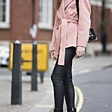 Under a light pink wrap coat and tucked into heeled boots for maximum coverage from the elements.