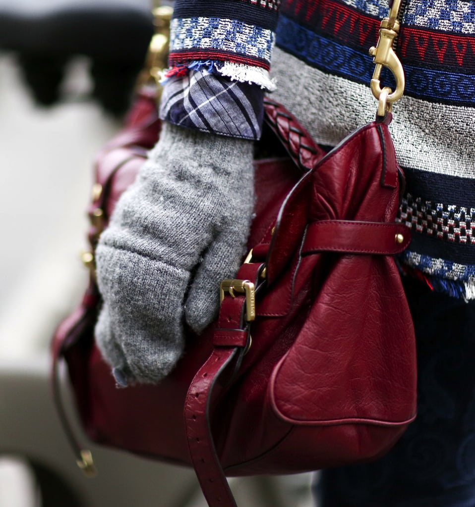 This Paris Fashion Week attendee matched her multicolored knits with a gorgeous dark red leather satchel.