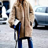 This fuzzy coat got a chic makeunder with a colorblocked bag, slim denim, and classic pumps.