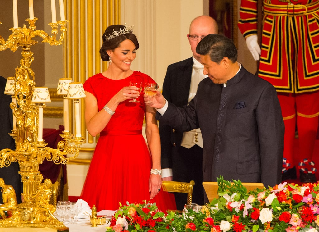 Usually, the first thing we notice about Kate Middleton's outfit is her dress — has she worn it before? Is it by one of her favorite designers? But at the duchess's first state dinner, which honored Chinese President Xi Jinping, we were captivated by her regal jewels, too — all of which were highly anticipated for the evening, especially since this was only Kate's third time wearing a tiara in public. Plus, she was recently given The Royal Family Order of Queen Elizabeth ll, a diamond-finished yellow badge to be pinned beneath the left shoulder. Kate swept up her hair to reveal chandelier earrings that perfectly played up her pearl-embellished Lotus (or Papyrus) tiara, which dates back to 1923 and was made by Garrard. It's not the first time the duchess has shown off the piece, but it just might be the best. Appropriately, Kate chose a sequin-embroidered red Jenny Packham gown, paying homage to China's flag. Read on for a look at her ornate ensemble, which is the epitome of bold elegance.