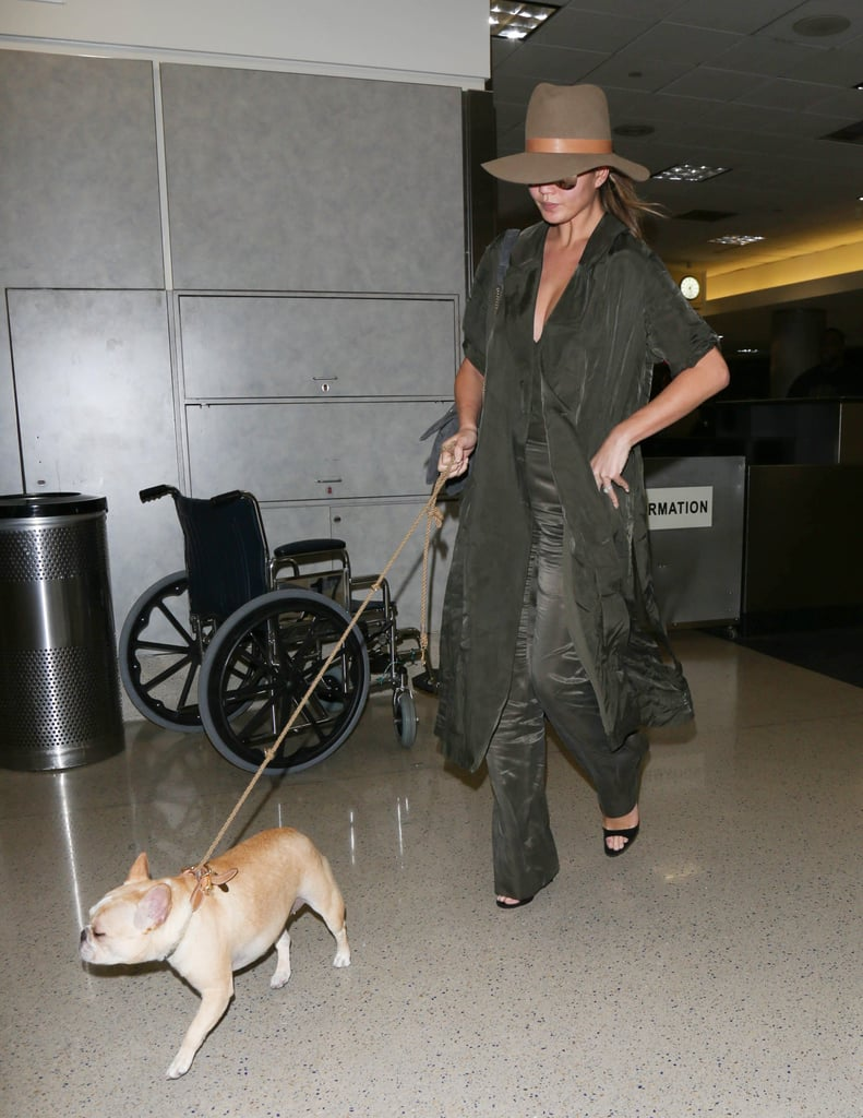 The model donned an army-green look at LAX, opting for satin flared pants, a duster coat, and a wide-brimmed hat.